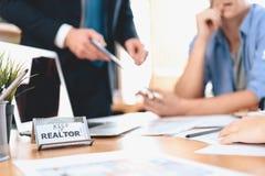 Grundstücksmakler, der am Schreibtisch im Büro sitzt Zeichen halten es wirklich, während Grundstücksmakler Vater, der Mutter und  lizenzfreie stockfotos
