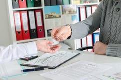 Grundstücksmakler, der seinem Kunden die Schlüssel übergibt Lizenzfreies Stockbild