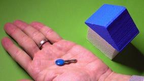 Grundstücksmakler, der Spielzeughaus mit blauem Dach und kleinen Schlüssel gegen grünen Hintergrund setzt Immobilienabkommenkonze Stockfotos