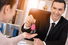 Grundstücksmakler gibt Frauenschlüssel mit keychain in der Form des Hauses zum neuen Haus Erwerb der Wohnung stockbild