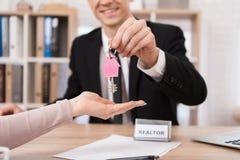 Grundstücksmakler gibt Frauenschlüssel mit rosa keychain in der Form des Hauses zum neuen Haus Erwerb der Wohnung stockfoto