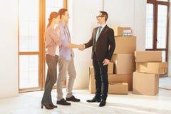 Grundstücksmakler mit Familie in der neuen Wohnung mit Pappschachteln Ehemann und Grundstücksmakler rütteln Hände lizenzfreie stockfotografie