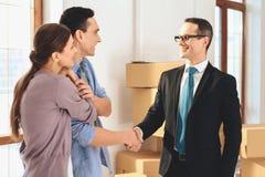 Grundstücksmakler mit Familie in der neuen Wohnung mit Pappschachteln Ehemann und Grundstücksmakler rütteln Hände stockfotografie