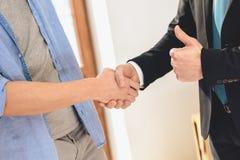 Grundstücksmakler mit Familie in der neuen Wohnung mit Pappschachteln Ehemann und Grundstücksmakler rütteln Hände lizenzfreies stockbild