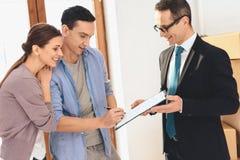 Grundstücksmakler mit Familie in der neuen Wohnung mit Pappschachteln Frau unterzeichnet Vertrag stockfoto