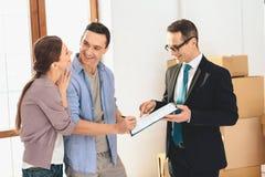 Grundstücksmakler mit Familie in der neuen Wohnung mit Pappschachteln Frau unterzeichnet Vertrag stockbild