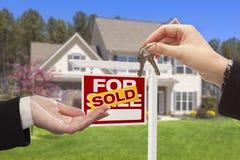 Grundstücksmakler, der die Haus-Schlüssel vor neuem Haus überreicht Stockfotografie