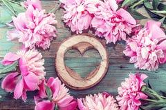 Розовые пионы и сердце высекли в древесине на старом покрашенном grunge Стоковые Изображения