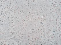 Grunge abstract gray background with the splashes of small pebbles pink and black color, speckled texture of asphalt. Stock Image