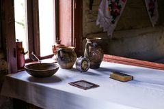 Grunge aged country style interior. Table with clay dishes, pottery. Stock Photos