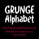 Grunge alphabet font. Hand drawn letters and numbers on a black background. Royalty Free Stock Images
