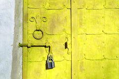 Grunge architectural background - aged bright yellow steel door Royalty Free Stock Photography