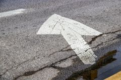 Grunge arrow painted on rough asphalt street by yellow curb and standing water stock image