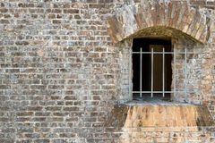 Brick Wall in Civil War Fort. Grunge scene backdrop featuring iron bar windows at Fort Pickens civil war site Royalty Free Stock Photography
