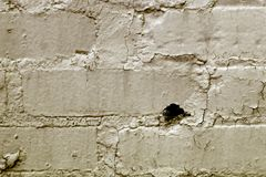 Grunge background. Peeling plaster on brick wall Stock Image