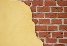 Grunge background. Yellow stucco and old red bricks under it Royalty Free Stock Photos