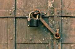 Grunge background - iron black padlock keeping the old door heck at the iron forged aged riveted door. Royalty Free Stock Image