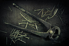 Grunge background with pliers and nails. Stock Photography