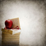 Grunge background with stack of books. Apple and eyeglasses Stock Photo