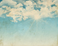 Grunge background of a sunny blue sky. Grunge style design of a sunny blue sky background with fluffy white clouds Royalty Free Stock Photography