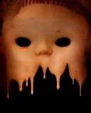 Grunge background with vintage evil spooky doll face. Grunge background with melting vintage evil spooky doll face and stucco texture Stock Photography