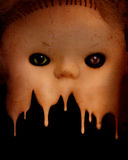 Grunge background with vintage evil spooky doll face. Grunge background with melting vintage evil spooky doll face and stucco texture Stock Photo