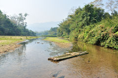 Grunge bamboo raft on river stream in forest landscape Royalty Free Stock Photos