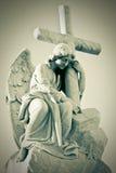 Grunge Bild eines traurigen Engels, der ein Kreuz anhält stockfoto