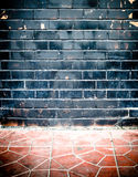 Grunge black brick wall and stone pavement floor.  Royalty Free Stock Photo