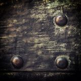 Grunge black metal plate with rivets screws background texture Stock Photography