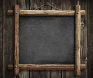 Grunge blackboard hanging on wooden wall background Royalty Free Stock Photography