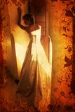 Grunge blond bride. Blond bride in sleeveless wedding dress against wall standing with her back on grunge swirls and scrolls background Stock Photo
