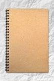 Grunge Braun-Abdeckungnotizbuch auf geknittertem Papier Stockbild