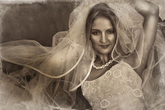 Grunge bride. Beautiful bride with large veil and silk wedding dress on grunge background with texture detail Stock Photos