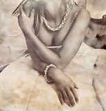 Grunge bride. Closeup of a beautiful bride in revealing dress wearing silver necklace on grunge stained background Royalty Free Stock Photography