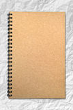 Grunge brown cover notebook on wrinkled paper. Background stock image