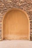 Grunge cement orange color door on bricks rock. Background Stock Photo