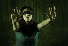 Dramatic composite of young scared and blindfolded Asian Korean teenager girl lost in dark forest confused playing dangerous royalty free stock image