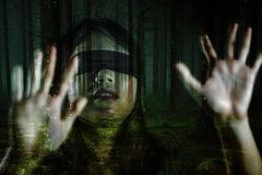 Dramatic composite of young scared and blindfolded Asian Korean teenager girl lost in dark forest confused playing dangerous. Grunge composite of young scared royalty free stock photos