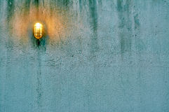Grunge Concrete Wall With Lamp. Blue grunge concrete wall with lamp and green moss for background or texture. Negative space can be used to put words or stock photography
