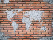 Grunge concrete world map on old brick wall. Background Stock Image