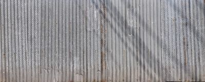 Grunge corrugated zinc fence with shadows on it Stock Images
