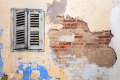 Grunge damaged brick wall with closed window. Background texture Stock Image
