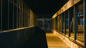 Grunge Dark Dirty Street with wired fence and yellow city lights leaking through sides with night light royalty free stock photography