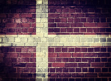 Grunge Denmark flag on a brick wall. Faded Denmark flag on an old brick wall background with a dark vignette Royalty Free Stock Photos
