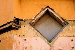 Grunge Diamond Window. Diamond shaped window on an old building in ruins and decay Royalty Free Stock Photo
