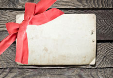 Grunge empty card and red bow on wood background Stock Photo