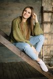 Grunge fashion: cute young girl informal model in blue jeans, dark knitted sweater and white socks sitting on the ladder stock photo