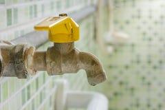 Grunge faucet in bathroom. Stock Photos