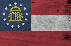 Grunge Georgia flag texture, The states of America, red white red, blue canton containing a ring of stars and coat of arms in gold. Flag of Georgia on wooden royalty free stock photography